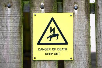 Danger of death sign on wooden fence