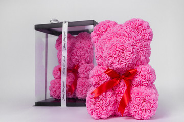Pink teddy bear toy of foamirane roses. The same teddy in clear box with black paper cover on background. Red stripe on teddy neck. Stock photo isolated on white background. Gift on holiday for women.