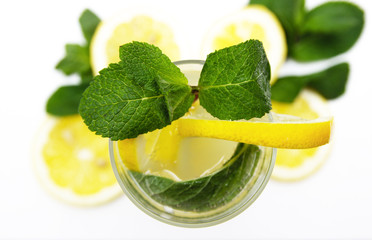 a glass of fresh lemonade, against a background of lemons and mint, isolated on a white background. top view.