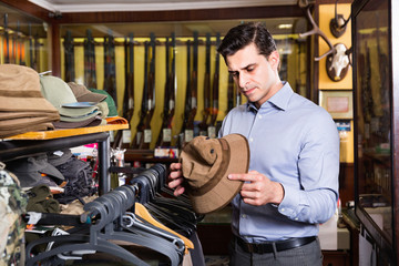 Portrait of man choosing hunting outfit in shop