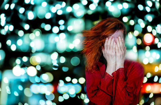 A woman covers her face with her hands. It is surrounded by bright lights.