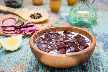 Pieces of raw beef liver soaked in milk in a wooden bowl and ingredients for cooking on the table
