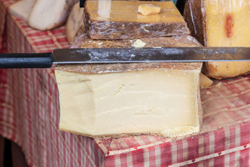 French cheese being cut with a traditional two handled knife
