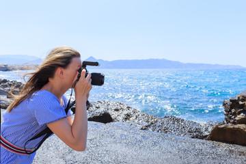 Woman photographer Nature photographer shooting the sea. Travel Concept