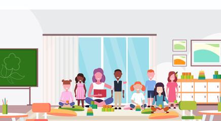woman teacher teaching mix race boys and girls preschool modern kindergarten children classroom with chalkboard desks chairs playground kid room interior full length flat horizontal