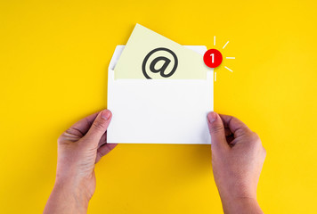 woman hands holds envelope with new mail notification icon and at sign