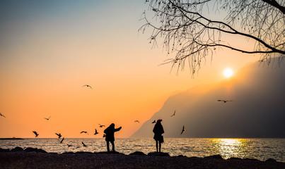 coppia osserva il tramonto al lago di Garda, italia