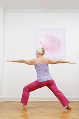 Senior woman with gray hair doing yoga exercises at home in front of a wall with a picture, asana warrior II