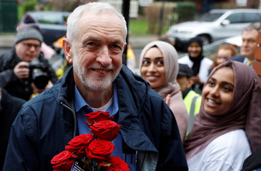 Britain's opposition Labour Party leader, Jeremy Corbyn, is greeted by young women and red roses during a visit to Finsbury Park Mosque, on Visit My Mosque day, in London