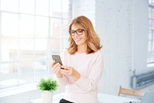 Attractive mature businesswoman using her mobile phone and text messaging