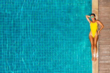 Gorgeous beautiful lady in sexy yellow bikini swims in a luxury hotel pool on an inflatable mattress. Summer holidays, travel, all inclusive. Top view on quadcopter