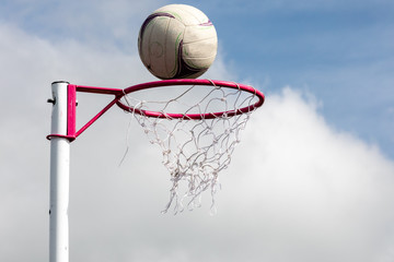 Netball post with ball about to go through the net