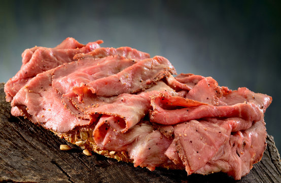 Roast beef open sandwich.  Rare roast beef, thinly sliced on thick slice of whole grain bread and lightly seasoned with black pepper.