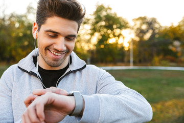 Handsome young sportsman outdoors in park listening music with earphones looking at watch.