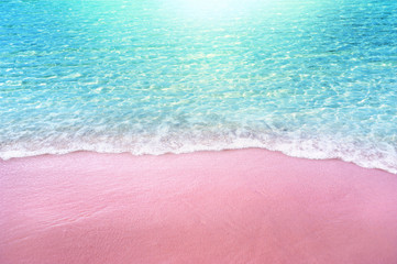 Wall Mural - pink sandy beach and soft blue ocean wave summer concept background
