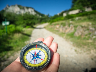 a compass and hand on road in mountains