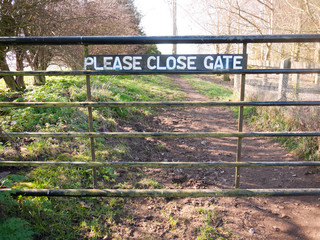 please close gate sign on metal closed gate outside country way