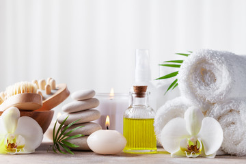 Spa, beauty treatment and wellness background with massage pebbles, orchid flowers, towels, cosmetic products and burning candles. Fototapete