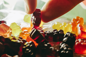 Close up fingers pick up jelly candy. Gummy bears. Healthy sweets