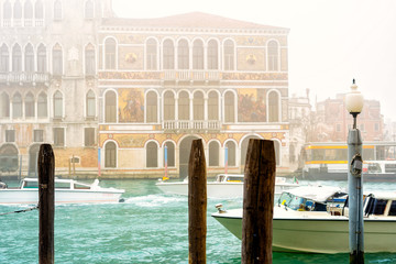 Typical bussy venetian street in misty spring day, Italy. Traditional venice canal in fog.