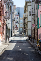 Narrow steep street in San Francisco with clean sidewalks and old fire escapes