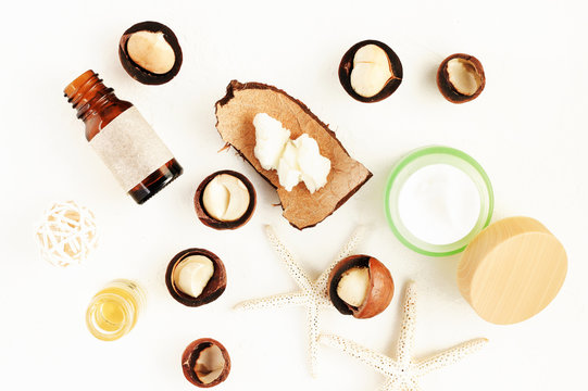 Macadamia nuts and body butter in jar and coconut shell, natural cosmetic product ingredients, top view white table