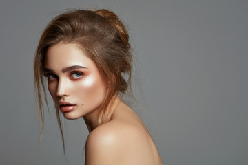 Glamour portrait of young woman with messy hair isolated over gray background