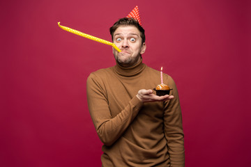 Picture of unhappy stressed young man having unhappy look, feeling tired and worn out with birthday party preparations, standing in studio