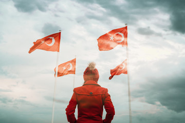Young Woman looking Turkish national flag and waving it in the sky.