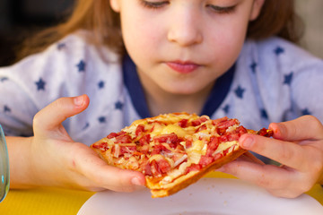 The child eats pizza.