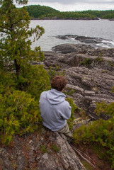 Man looking out to rocky shoreline