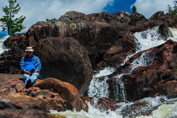 senior male resting on rocks near waterfall