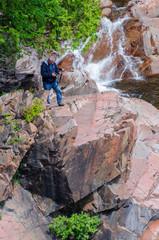 Man standing on rock near waterfall