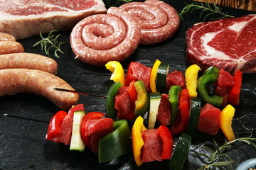 Assorted delicious raw meat with vegetable on a barbecue with t-bone steak, sausages and meat Skewers.