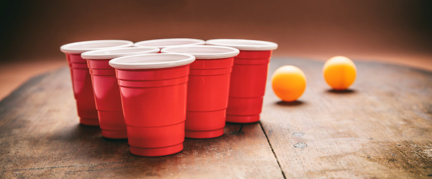 Beer pong. Plastic red color cups and ping pong balls on wooden background