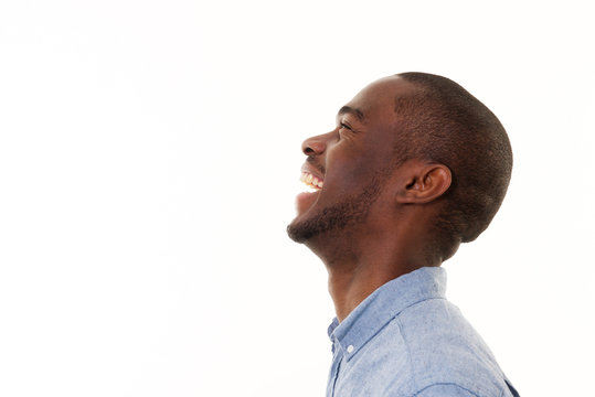 profile portrait of handsome young black man laughing against isolated white background