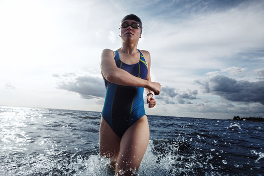 Young woman in swimsuit running in the water during triathlon competition