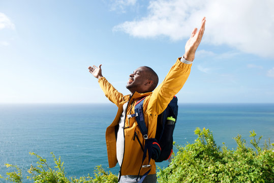 happy young african american male traveler with arms open outdoors