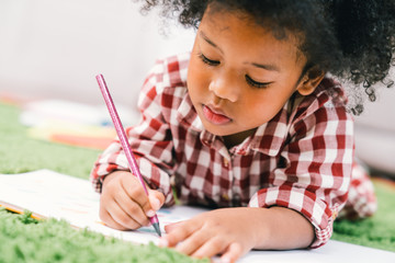 Cute young African American kid girl drawing or painting with colored pencil. Kindergarten children...