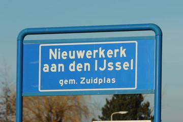 Blue and white sign  to mark the start of the urban area in Nieuwerkerk aan den IJssel in the Netherlands