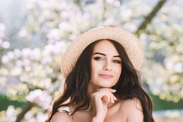 Outdoor close up portrait of young beautiful happy smiling lady with long dark hair, makeup, wearing straw hat, posing near blooming tree. Copy, empty space for text
