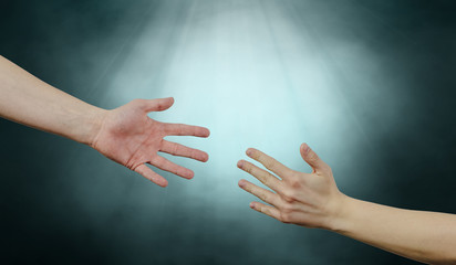 Help and help each other, reaching out for a helping hand. The hand is trying to grab the other hand. View of two hands on a bright gray background. Indifference to harm. Wall mural