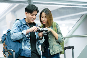 Young hipster couple in love with backpacks looking camera's monitor checking pictures taken in the airport waiting Departure . Travelling concept.
