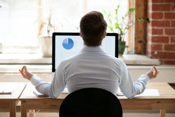 Rear view businessman sitting at desk opposite pc doing yoga