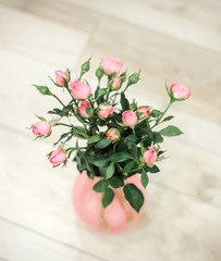 Sweet pink roses flowers in vases on beige painted wooden background.