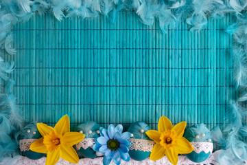 Wielkanowcne błękitne tło z niebieskimi pisankami i żółtymi żąkilami