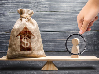 Magnifying glass is looking at a money bag with up arrow and man figurine on scales. Criteria and requirements for increasing the work of a specialist. The average salary in the labor market, pricing.