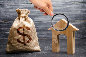 Magnifying glass is looking at a bag with money and a house with a large doorway. Concept of real estate acquisition and investment. Affordable cheap loan, mortgage. Taxes, income. Building houses