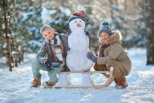 Children make a snowman. Children building a snow man playing outside on a sunny snowy winter day. Outdoor family holiday on the Christmas holidays. Boys play snowballs. Winter clothes