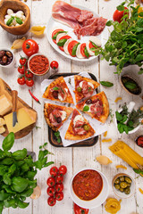 Italian food ingredients on old wooden background, top view.